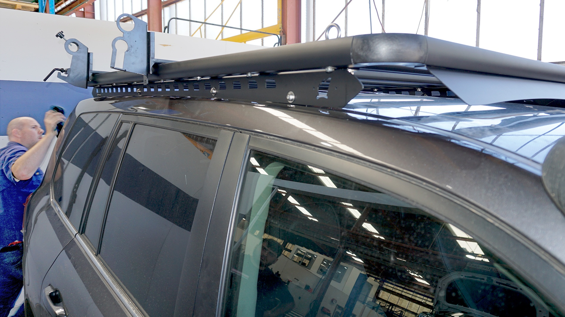 Side view of a Toyota LandCruiser 200 Series roof with a Wedgetail roof rack installed on one piece mounting rails and a hi-lift jack and shovel holder installed as well as five tie-down eyelets.