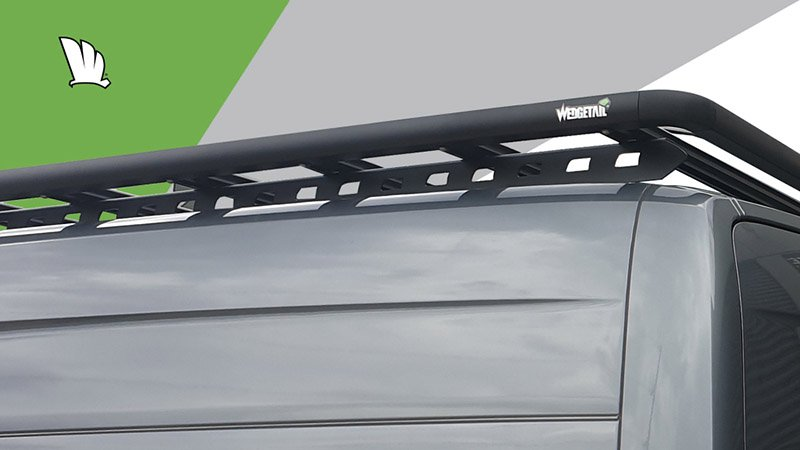 Rear corner of a Mercedes-Benz Sprinter with a Wedgetail roof rack installed showing the one piece mounting rail and the roof rack platform mounted to the top of the rail.