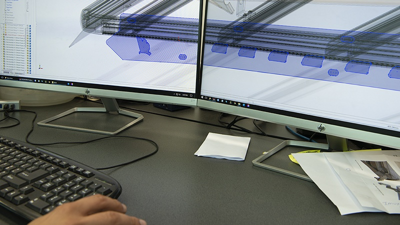 The Wedgetail roof racks were developed using a CAD system shown here with a drawing on the computer monitors.