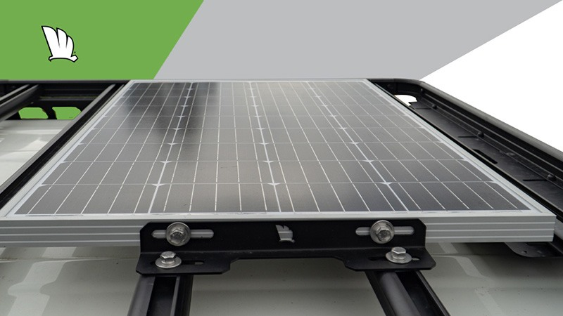 A solar panel mount kit in place with the panel held in place by four mounting bolts.